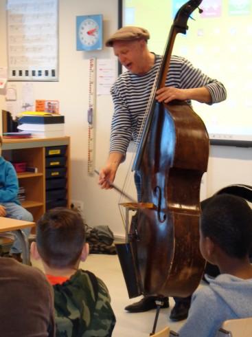 Een gast in de klas vertelt over zijn instrument en laat horen hoe het klinkt.